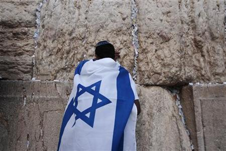 An Israeli youth wrapped in a national flag prays at the Western Wall, Judaism's holiest prayer site, in Jerusalem's Old City on Jerusalem Day May 20, 2012. REUTERS/Darren Whiteside/Files